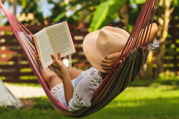 Beautiful woman relaxing in hammock. Beautiful woman reading book in hammock. Happy beautiful woman in white dress relaxing in hammock. Beautiful woman in vacation. Vacation. Hammock. Tropical garden.